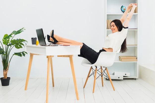 Frau, welche die arme bei tisch sitzen im büro ausdehnt
