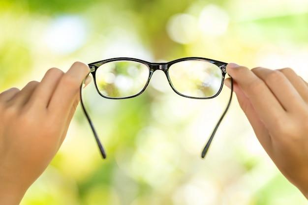 Frau, welche die brille des blauen auges mit glänzendem schwarzem rahmen auf grünem hintergrund hält