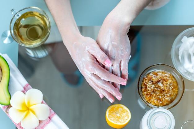 Frau, welche die creme auf den händen befeuchtet und sie mit naturkosmetik ernährt aufträgt. hygiene und pflege für die haut