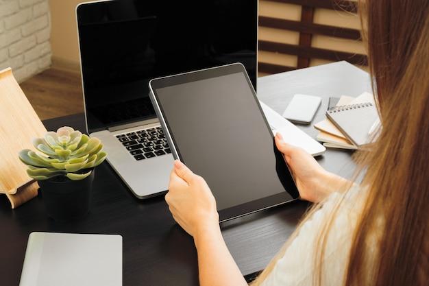 Frau, welche die digitale tablette sitzt an einem tisch in einem büro verwendet