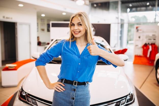 Frau, welche die gefühle stehen vor einem auto zeigt