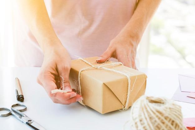 Frau, welche die geschenkbox auf tabelle einwickelt