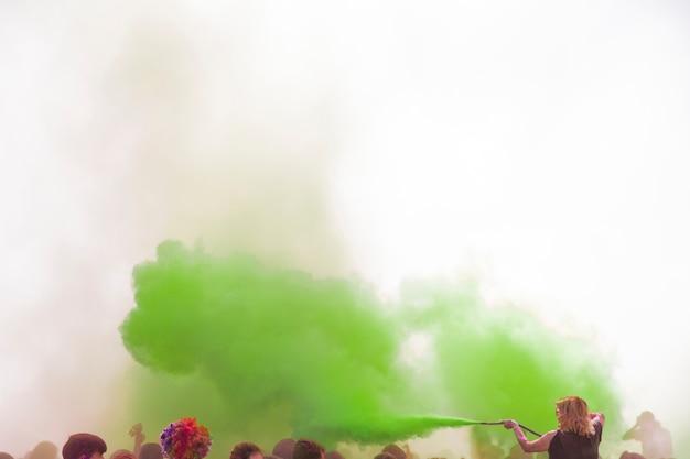 Frau, welche die grüne holi farbe mit rohr über der masse sprüht