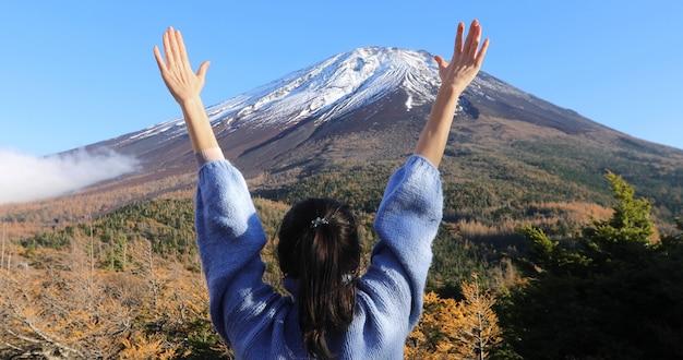 Frau, welche die hände grüßen schneebedeckten berg anhebt