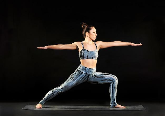 Frau, welche die haltung des kriegers 2 im yoga demonstriert