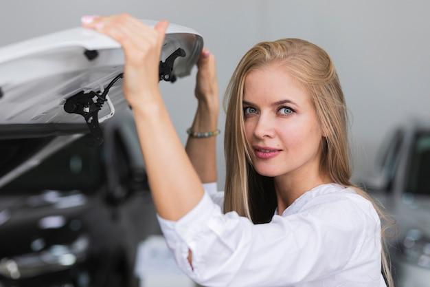 Frau, welche die haube betrachtet kamera hält