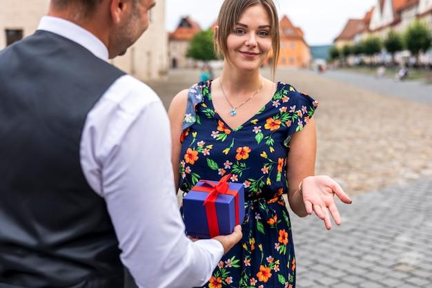 Frau, welche die kamera beim empfangen eines geschenks betrachtet