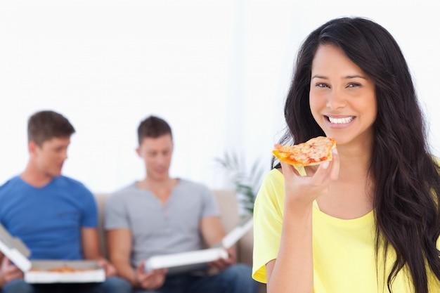 Frau, welche die kamera lächelt und betrachtet, wie sie pizza hält