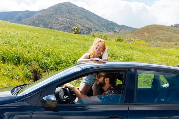 Frau, welche die kamera setzt hände auf dach aus autofenster heraus betrachtet