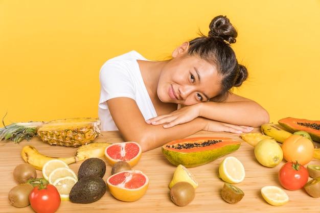 Frau, welche die kamera umgeben durch früchte betrachtet