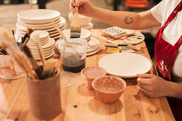 Frau, welche die keramische farbe nimmt, um auf platte mit pinsel zu malen