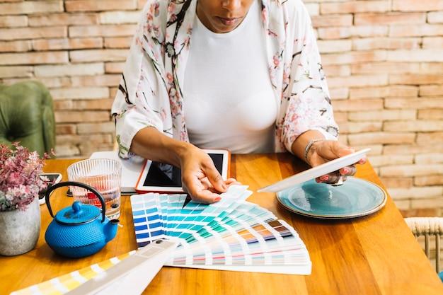 Frau, welche die keramische platte mit farbmuster auf holztisch zusammenbringt