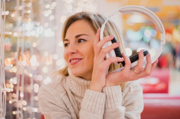Frau, welche die kopfhörer betrachten weihnachtslichter hält