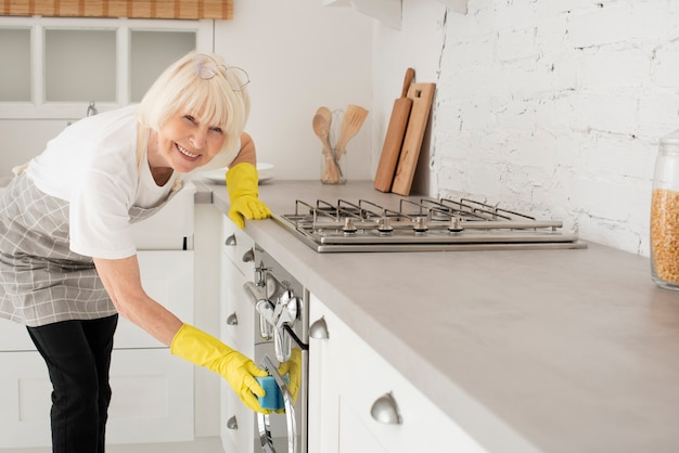 Frau, welche die küche mit handschuhen säubert