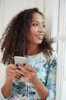 Frau, welche die musik auf smartphone genießt