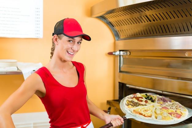 Frau, welche die pizza in den ofen drückt