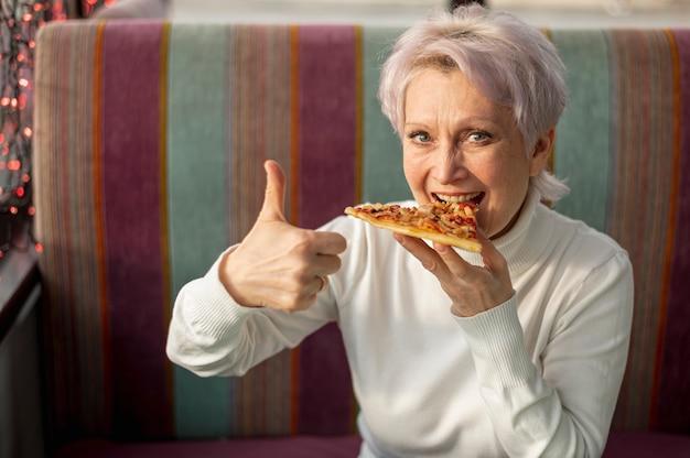 Frau, welche die pizza zeigt okayzeichen isst