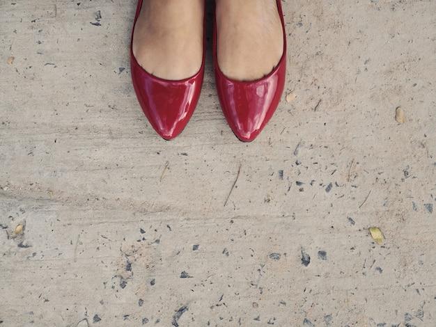 Frau, welche die roten lederschuhballerinen stehen auf grauem konkretem boden trägt.
