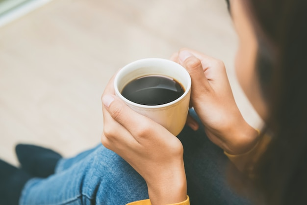 Frau, welche die schale heißen schwarzen kaffee sich zu hause entspannt hält