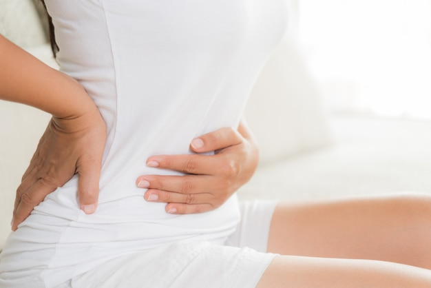 Frau, welche die schmerzlichen magenschmerzen sitzt auf sofa hat. chronische gastritis. bauch aufgedunsen conc