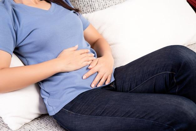Frau, welche die schmerzlichen magenschmerzen zu hause liegen auf sofa hat. konzept der chronischen gastritis