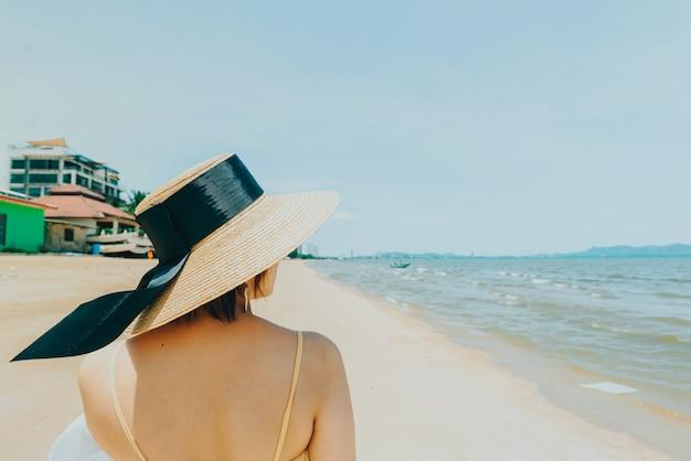 Frau, welche die strandentspannung froh im sommer durch tropisches blaues wasser genießt.
