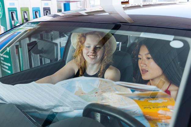 Frau, welche die straßenkarte sitzt im auto studiert