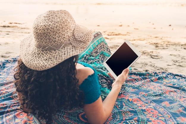 Frau, welche die tablette liegt am strand verwendet