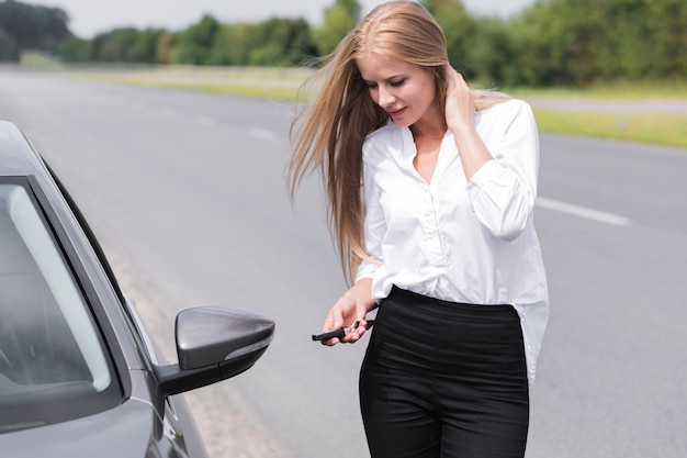 Frau, welche die türen des autos schließt