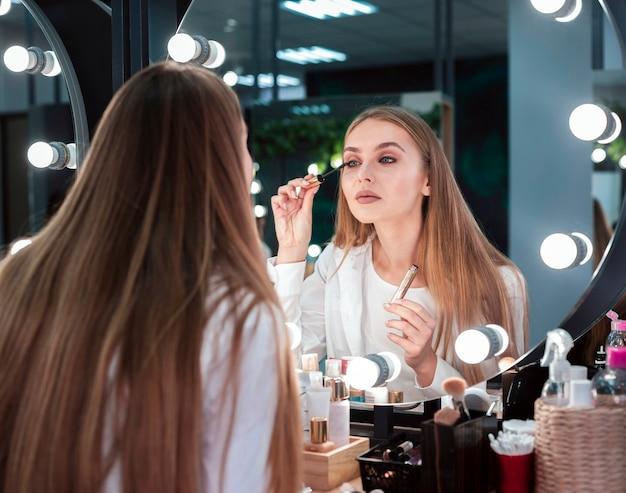 Frau, welche die wimperntusche betrachtet spiegel anwendet