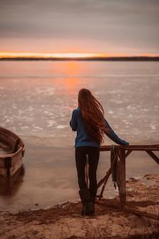 Frau, welche die zeit sich entspannt durch den schönen see bei sonnenaufgang genießt