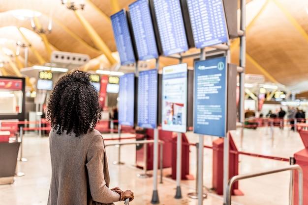 Frau, welche die zeitplaninformationstafel im flughafen mit einem koffer betrachtet