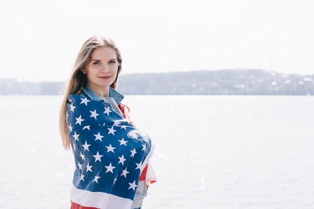 Frau, welche ernsthaft die kamera eingewickelt in der amerikanischen flagge betrachtet