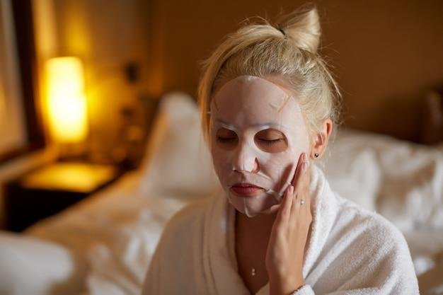 Frau wendet blattmaske auf ihrem gesicht im schlafzimmer an