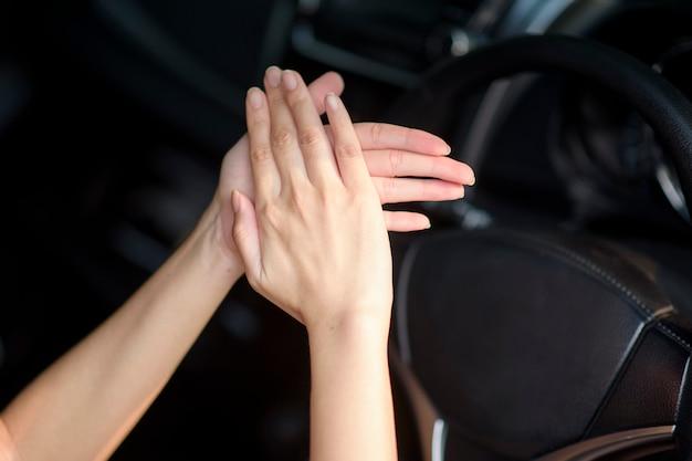 Frau wendet händedesinfektionsmittel auf ihre hände im auto an