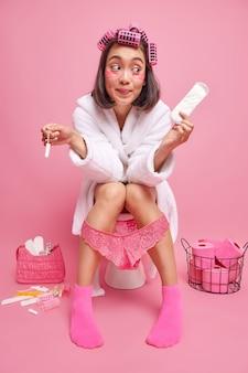 Frau wendet lockenwickler an hält damenbinde und tampon, gekleidet in weißen bademantel rosa socken ertrunkenes höschen sitzt auf toilette isoliert über rosa