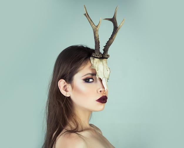Frau widder in tierschädelhörnern. junge hexe. frau hexe, halloween. schönheit der frau mit tierschädel und geweih.
