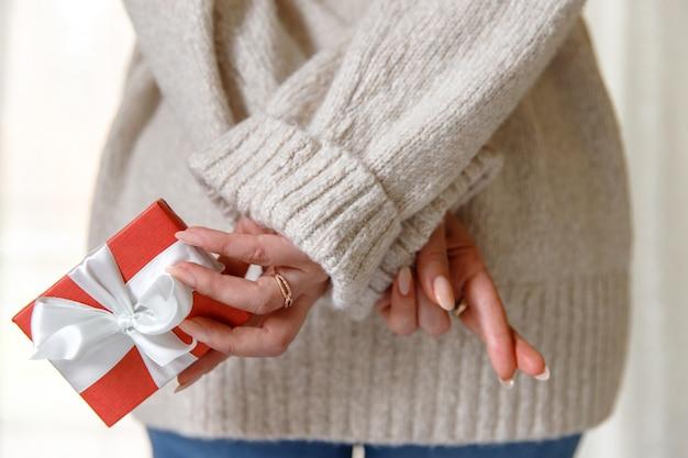 Frau will ihrem freund eine geschenküberraschung in einer roten schachtel geben und besorgt, daumen drücken, blick von hinten.