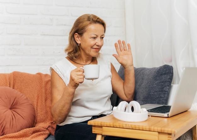 Frau winkt freunden zu, während sie einen videoanruf hat