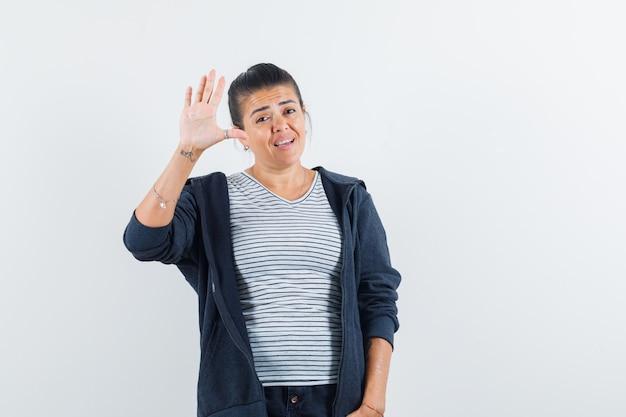 Frau winkt hand, um sich im t-shirt zu verabschieden