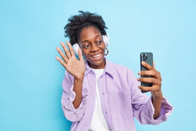 Frau winkt palm in hallo-geste macht videoanruf grüßt freund aus dem ausland hält smartphone lächelt breit trägt stylisches lila hemd isoliert auf blau