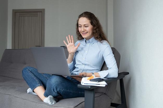 Frau winkt zur kamera des laptops