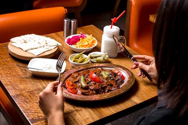 Frau wird iskender kebab in kupferplatte mit eingelegtem joghurt und ayran serviert