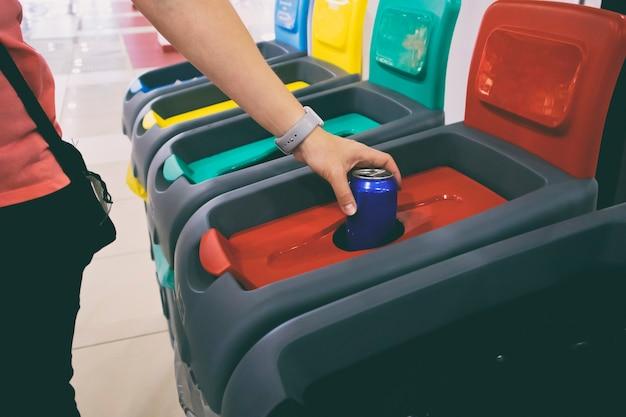 Frau wirft aluminiumdose in einen von vier behältern, um müll zu sortieren