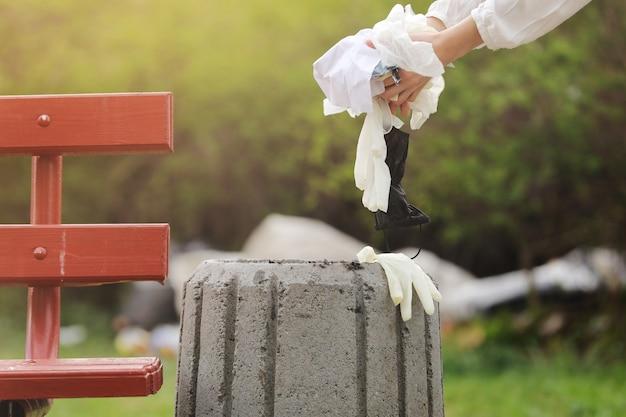 Frau wirft plastikmüll in den müll. frauenhand, die müllplastik für die reinigung am park aufhebt. müllabfuhr nach einer pandemie. selektiver fokus