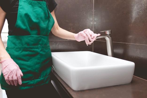 Frau wischt den wasserhahn im badezimmer für einen glanz ab