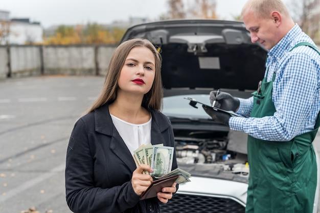 Frau zählt geld, um autoservice zu bezahlen