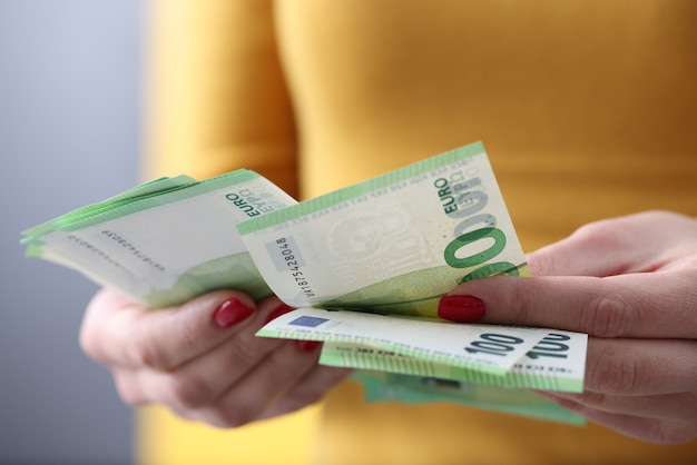 Frau zählt hundert euro-scheine. lohn- und gehaltsabrechnungskonzept