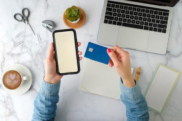 Frau zahlen online per kreditkartenlink zum smartphone und zur website. online-banking und shopping-konzept. draufsicht, flach liegen.