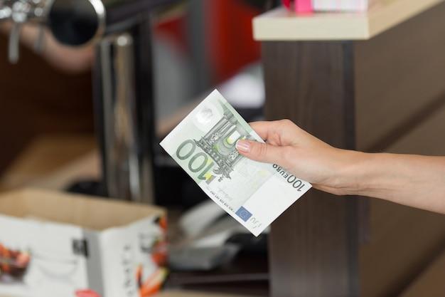 Frau zahlt bargeld für das frühstück im café mit euro-banknoten. nahaufnahme.